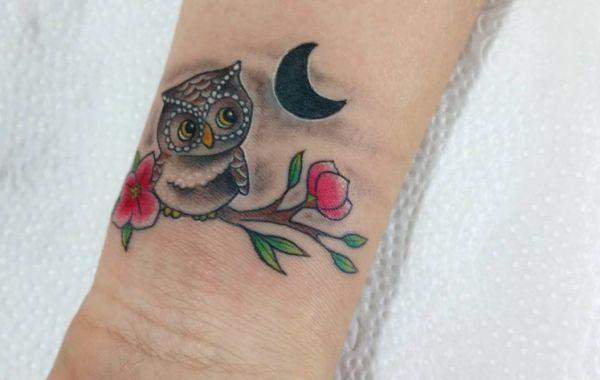Eule Tattoo mit Halbmond und Blumen am Handgelenk