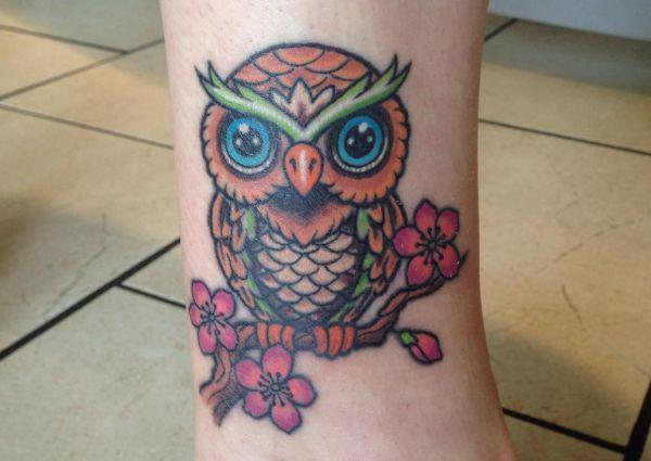 Eule Tattoo mit Blumen am Knoechel