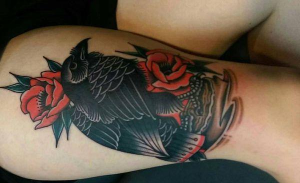 Rabe mit Blumen Tattoo am Unterschenkel Frau