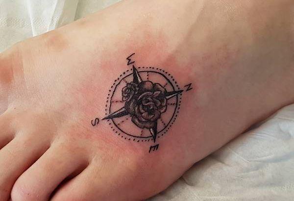 Kleine Kompass Tattoo mit Blume am fuß