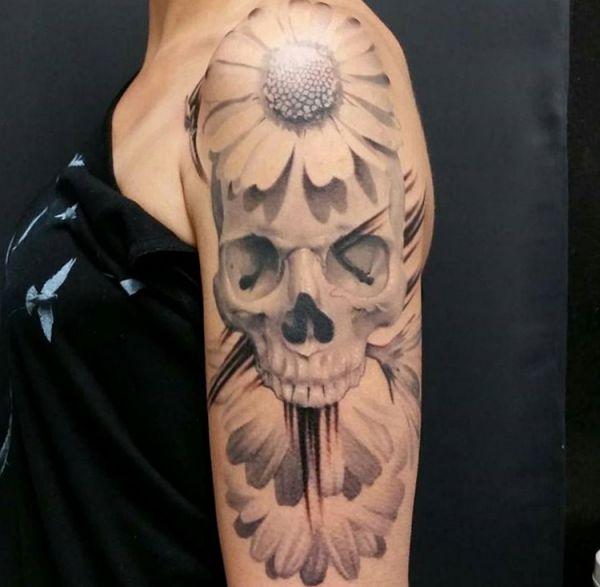 Totenkopf und Gänseblümchen Tattoo am Oberarm