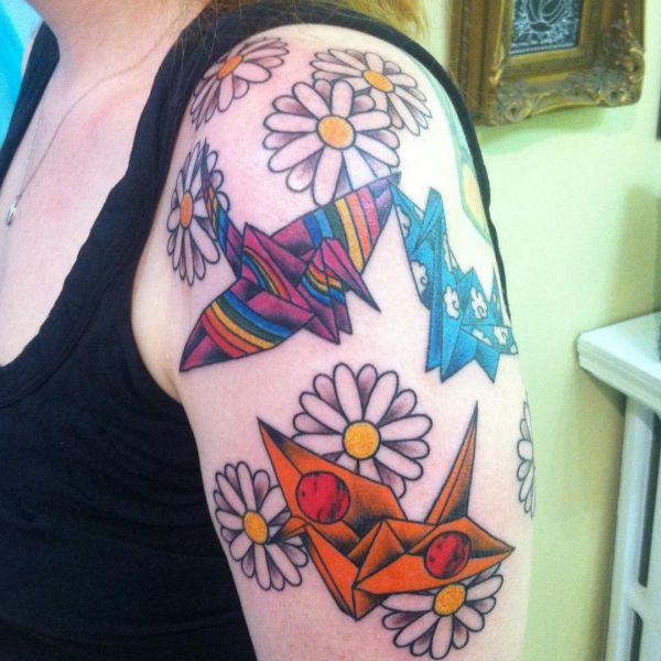 Gänseblümchen und Origami Kranich Tattoo am Oberarm