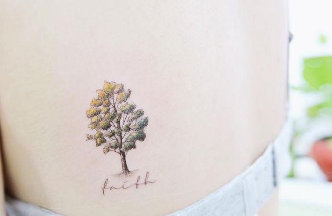 Kleiner Baum mit Namen Tattoo am Schulterblatt