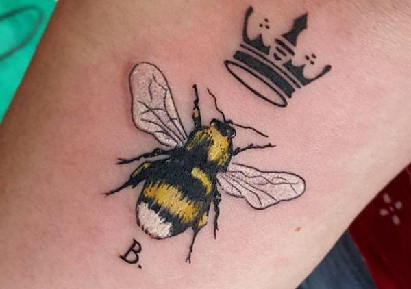 Bienenkönigin mit Krone und Initialen auf dem Arm