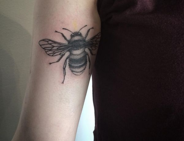 Bienen Tattoo am Oberarm Schwarz