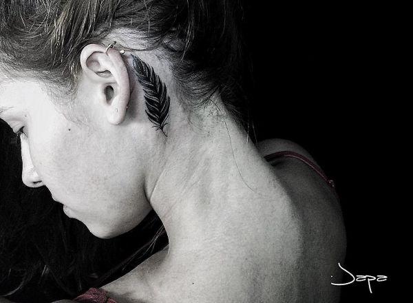 Feder Tattoo hinter dem Ohr für Frau