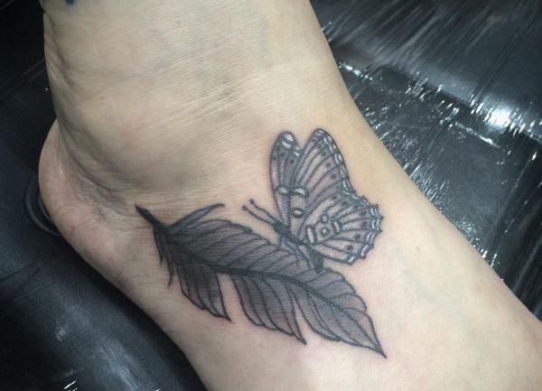 Feder mit Schmetterling Tattoo am Fuß für Frau