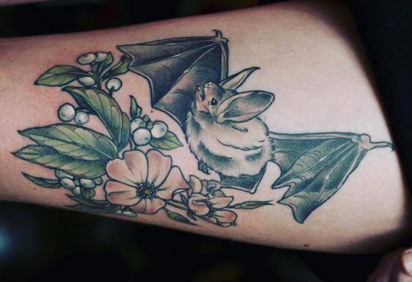 Fledermaus mit Blumen Tattoo am Oberschenkel