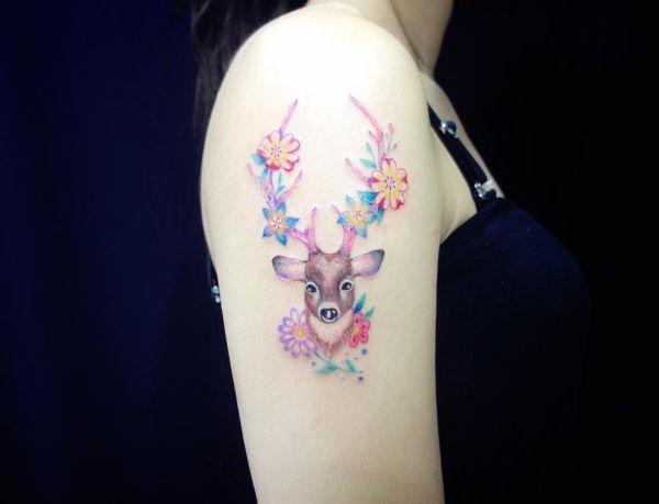 Hirschkopf mit Blumen Tattoo Design am Oberarm Frau
