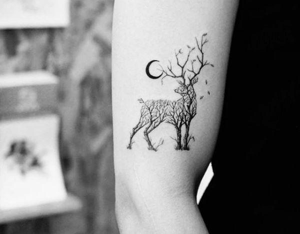 Abstrakt Hirsch und Halbmond Tattoo am Oberarm