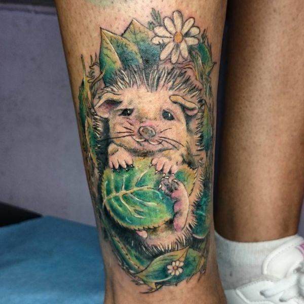 Tattoo Igel mit Blatt und Blüte am Unterschenkel