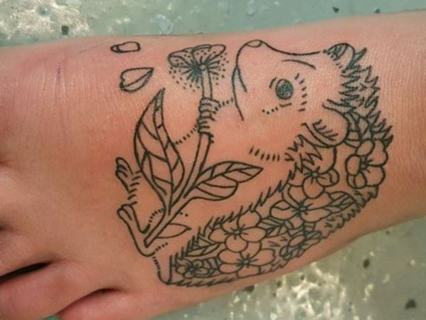 Igel mit Blume Tattoo Design Schwarz am fuß