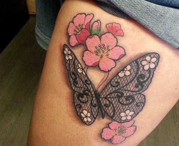 Spitze Schmetterling und Kirschblüten Tattoo am Oberschenkel