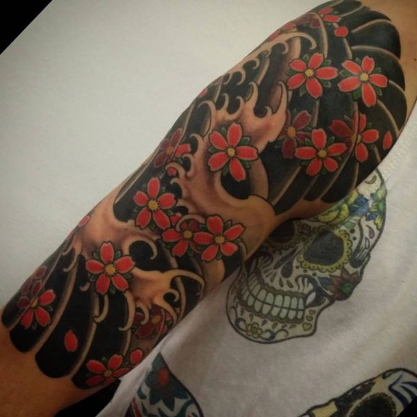 Wellen und Kirschblüten Tattoo auf dem Arm