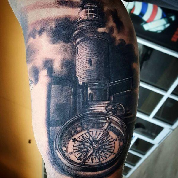 Kompass mit Leuchtturm schwarz und weiß auf der Bein