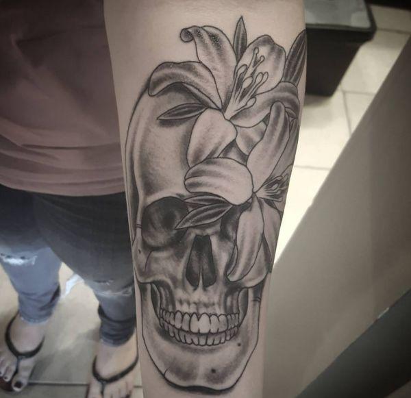 Lilie und Totenkopf Tattoo Design am Unterarm