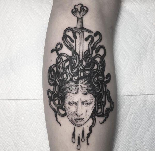 Medusa mit Schwert Tattoo auf der Bein