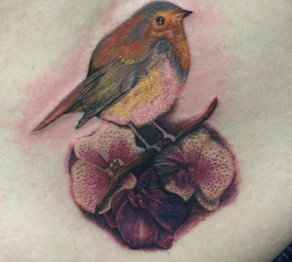 Orchidee Tattoo mit Vogel am Unterer Rücken