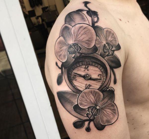 Orchidee Tattoo mit Kompass am Oberarm der Männer