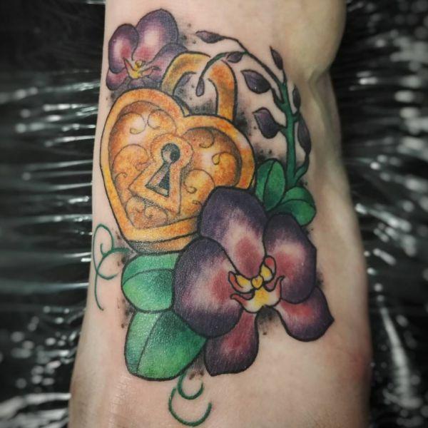 Vorhängeschloss mit Orchidee Tattoo am Fuß