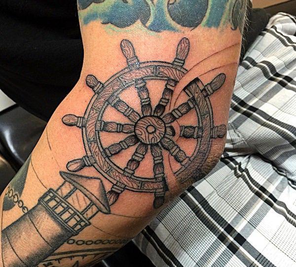 Leuchtturm und Schiffs-Rad auf dem Arm