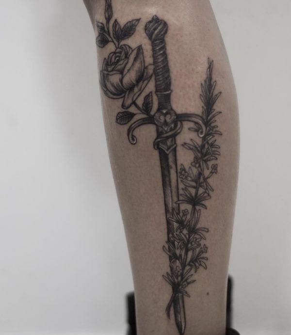 Schwert Tattoo mit Rose auf der Bein