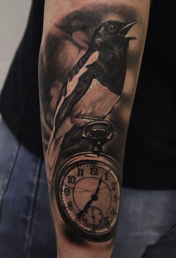 Elster und Uhr Tattoo auf dem Arm