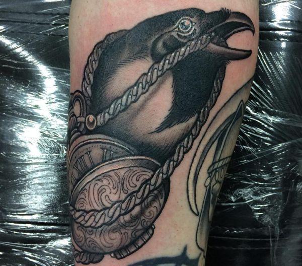 Elster mit Uhren Tattoo auf dem Arm