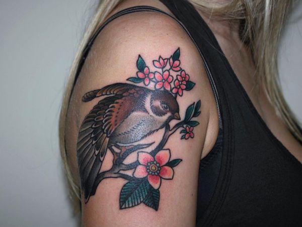 Spatz mit Blumen am Oberarm für Frau
