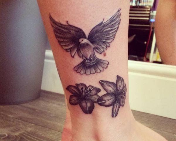 Taube mit Blumen am Unterschenkel