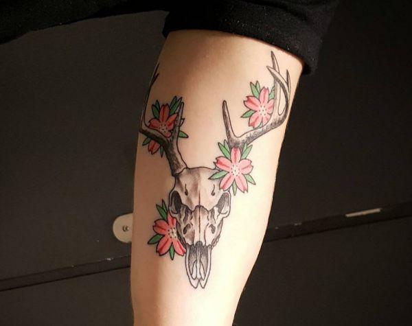 Hirsch Totenkopf mit Blumen Tattoo am Oberarm
